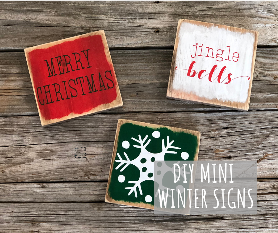 mini wooden signs for winter. Signs read MERRY CHRISTMAS, JINGLE BELLS, and an image of a white snowflake. Signs are painted on pieces of 1x6 and looked rustic and distressed.