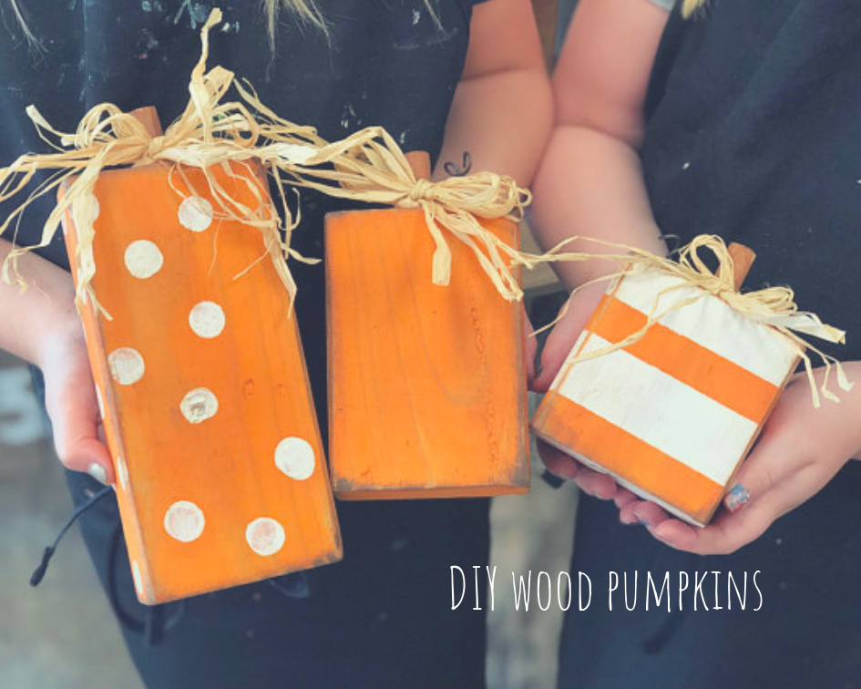 orange painted pumpkins made from a 2x4 piece of lumber. Tallest pumpkins is orange with white polka dots. Middle sized pumpkin is solid orange with distressing. Smallest pumpkin is orange with white stripes. Each pumpkin has a dowel rod stem and a raffia bow on top of the pumpkin. Pumpkins are being held in hands.