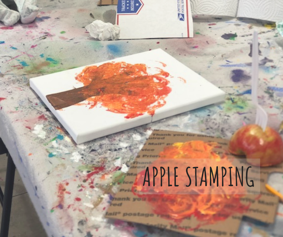 white canvas with fall tree painting done by a preschooler. Apple stamping art using half of an apple dipped in fall colored paints