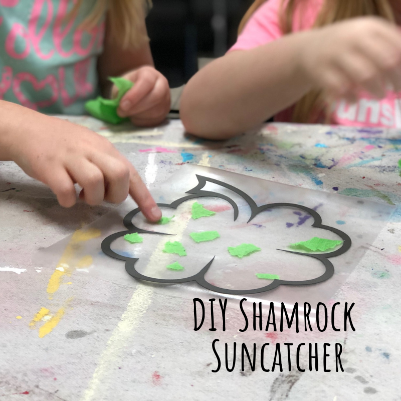 little girls making a St. Patrick's Day easy craft. Attaching pieces of green tissue paper to sticky clear contact paper. There is a black cardstock cutout of a 4 leaf clover or shamrock
