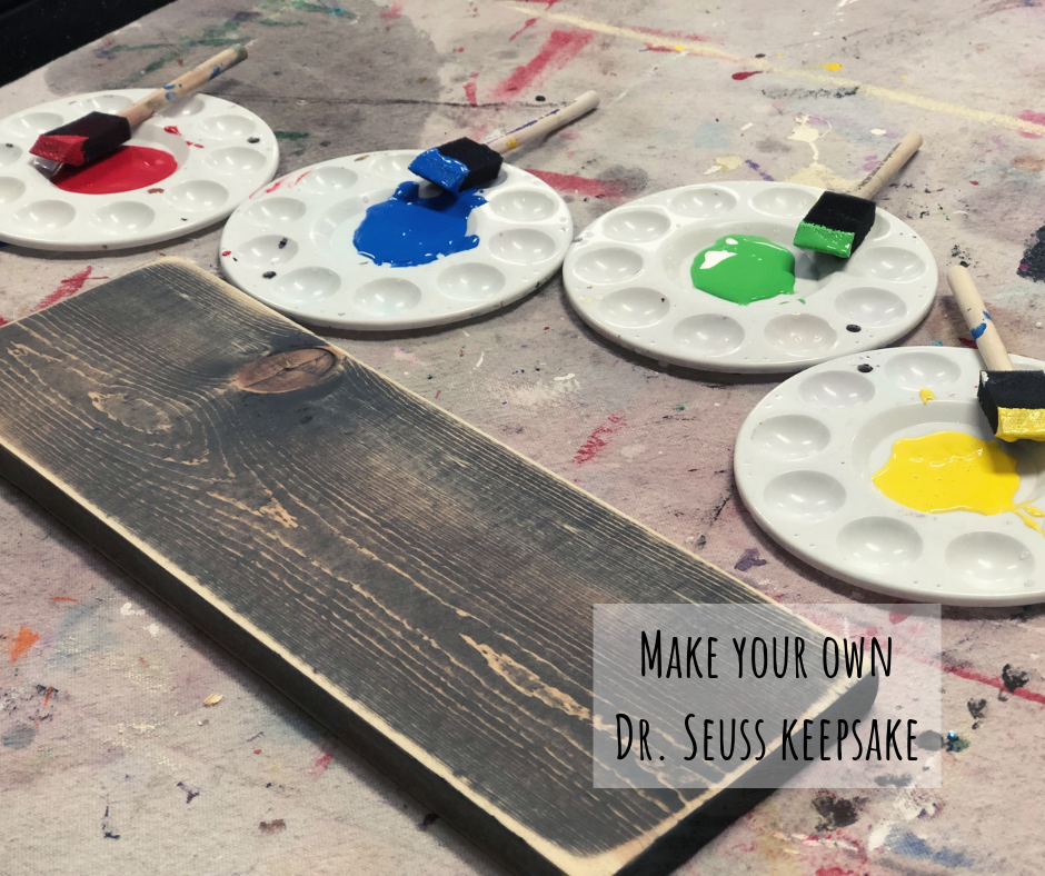 """distressed gray stained board. Colorful paint pallets surround the wood sign, red, blue, green, yellow. Each paint color has a black tipped wood handle 1"""" foam brush inside the paint"""