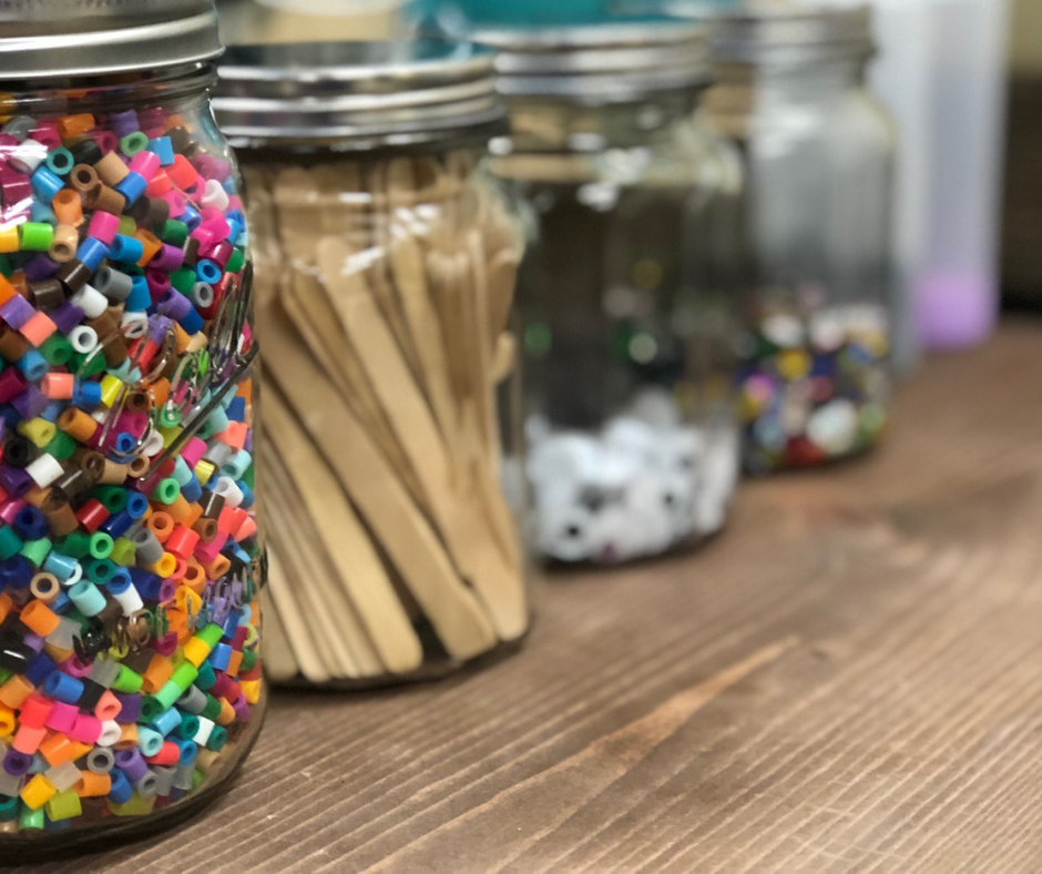 mason jars filled with small pony beads, popsicle sticks, googly eyes, rhinestones. Clear craft storage containers