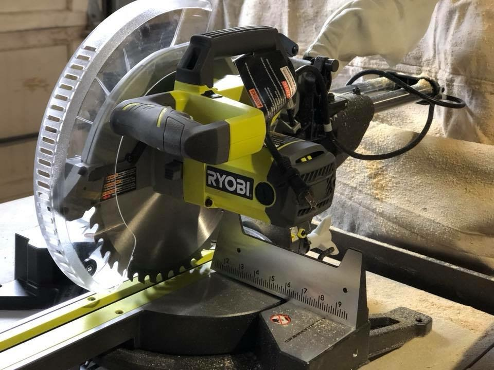 "12"" sliding Ryobi miter saw. sitting on a table in a garage"