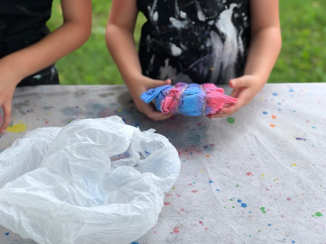 Little girl holding a twisted and coiled rubber banded white t-shirt that has had red and blue food coloring squirted on it to tie dye. There is a clear plastic bag next to her to put the t-shirt in and a canvas drop cloth on the table to protect the surface from stains.
