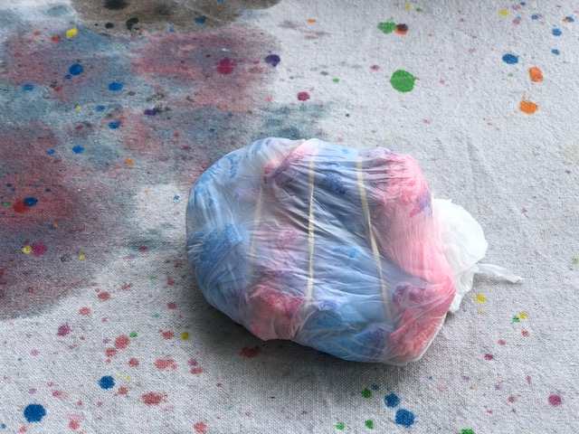 plastic bag wrapped red and blue tie-dyed t-shirt sitting on a canvas drop cloth to protect the table from stains.