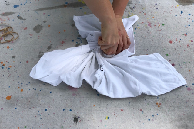 how to tie dye using food coloring. Basic folding and twisting technique used for easy tie dying for kids. Girl twisting a white shirt for tie dying
