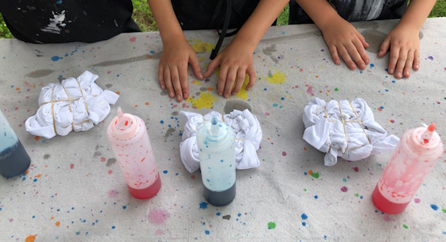 Clear condiment squeeze bottles filled with red and blue food coloring and water for tie dying. White t-shirts twisted up with rubber bands wrapped around them read for a basic tie-dying technique using no chemicals.