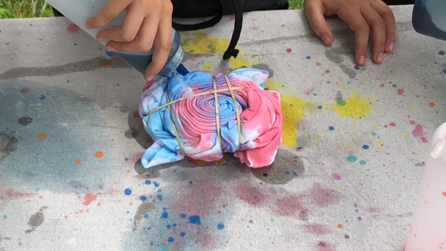 Little girl using red and blue food coloring to tie-dye. She is using a clear condiment bottle to squirt the food coloring and water mixture onto the coiled and rubber band wrapped t-shirt. The shirt is on a canvas drop cloth to protect the surface.