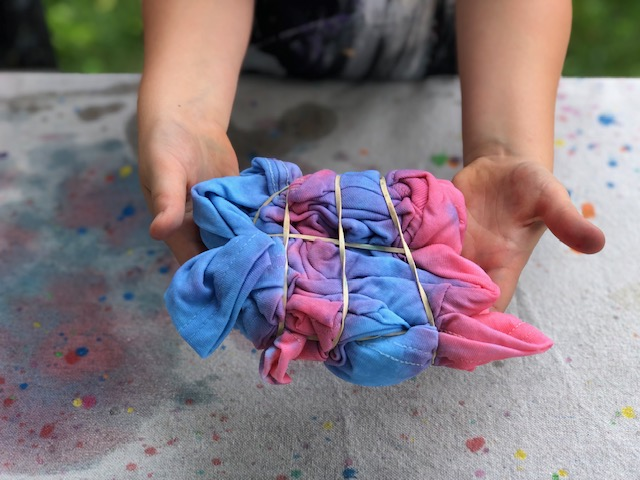 tie-dye with food coloring. Learn different folding techniques of tie-dying with a washable alternative. Kid friendly tie-dye method with no chemicals. Child holding a tie-dye shirt that is wrapped with rubber bands and colored red white and blue.