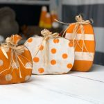 small, medium, and large free-standing wood pumpkins. Smallest pumpkin is painted orange with white polka dots and raffia bow tied around the wood stem. Medium pumpkin is white with painted orange polka dots and raffia tied around the wood stem. Large pumpkin is painted orange with white stripes and a raffia bow tied around the wood stem. All 3 pumpkins are distressed around the edges and have antiquing wax. There are wood candy corn in the background.