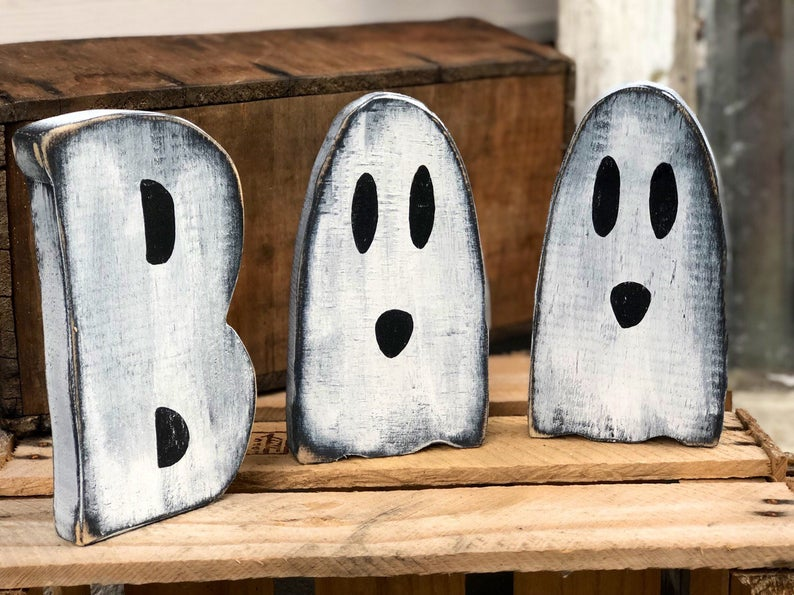 """White letters reading BOO with the cute ghosts replacing the letter """"O"""". Wood letters are painted white with black accent color. They are distressed for a rustic look"""