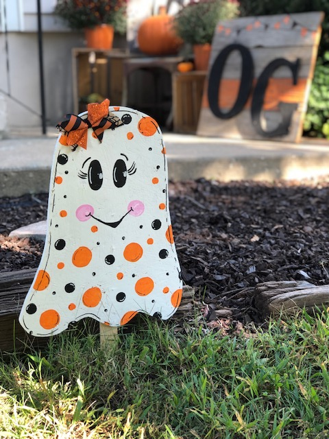 girl ghost yard stake. Ghost is painted in white with orange and black polka dots of varied sizes scattered on the front of the ghost. Ghost has rosy cheeks, eyelashes, and is smiling. She has a Halloween orange and black striped glittery bow on the top of her ghost head.