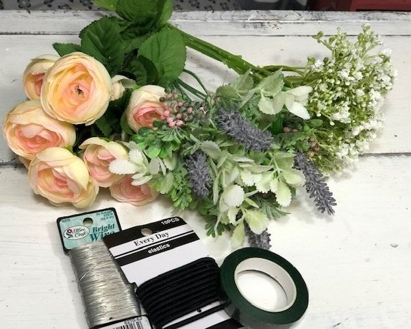 materials need to make a fake flower wrist corsage. Faux spring blush colored roses, baby's breath, lavender, lambs ear, silver thin wire, green floral tape, hair elastics, on a white wash shiplap background table.