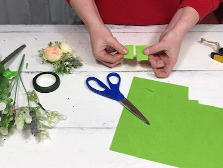women cutting rectangles from green pieces of felt. She has fake spring florals on the table. She is wearing a red sweatshirt and using scissors with blue handles.