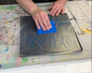 using a vinyl squeegee on painted wood signs