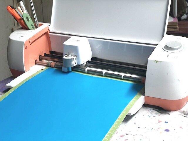 salmon colored Cricut cutting machine cutting blue transparent oramask 813 stencil film in a craft room