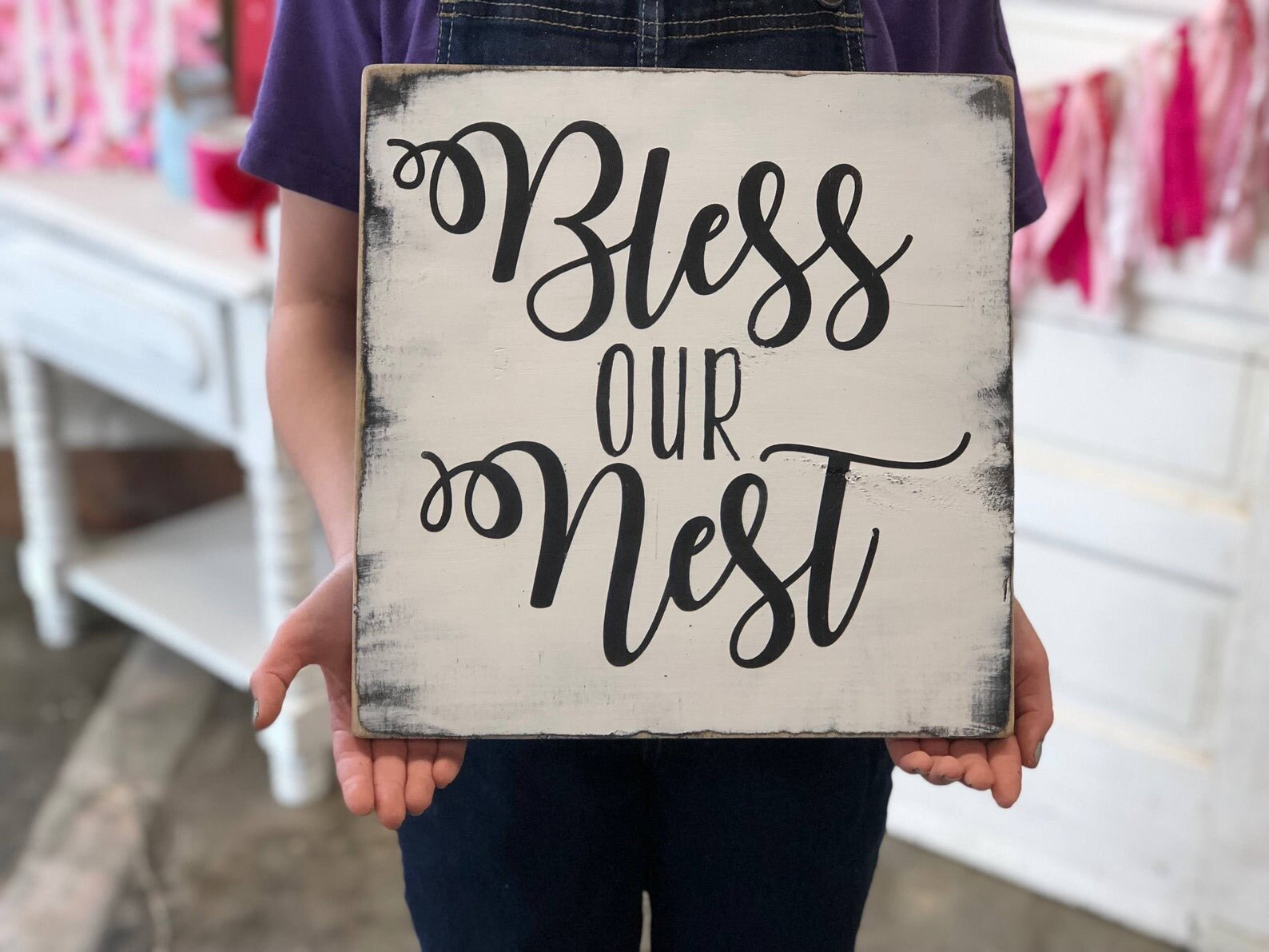 """girl holding a 12""""x12"""" white painted wood sign that reads bless our nest in cursive and skinny font painted in black with black distressed edges"""