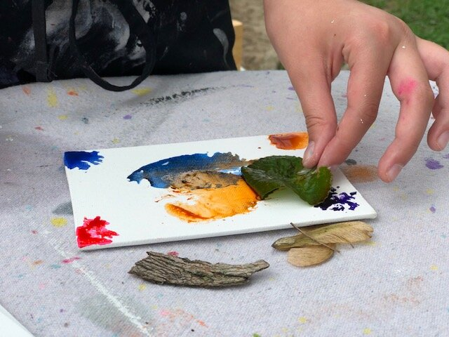 child using a leaf to paint colorful prints on a white mini canvas