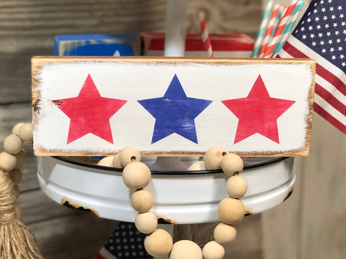 light colored stained wood sign painted white distressed background. three 3 red and blue patriotic stars are painted on the front of the sign. Wood bead garland and an American flag