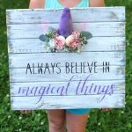 little girl holding a distressed white plank sign that reads always believe in magical things. It has a unicorn horn with ears and a blush colored floral crown around the glittery purple unicorn horn.