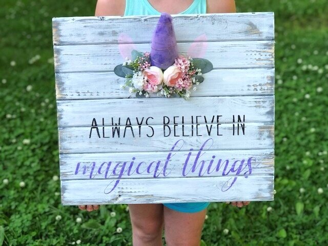 UNICORN ROOM DECOR - little girl holding a distressed white plank sign that reads always believe in magical things. It has a unicorn horn with ears and a blush colored floral crown around the glittery purple unicorn horn.