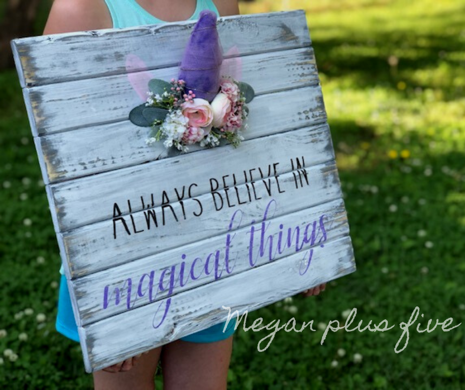 UNICORN ROOM DECOR- little girl holding a distressed white plank sign that reads always believe in magical things. It has a unicorn horn with ears and a blush colored floral crown around the glittery purple unicorn horn.