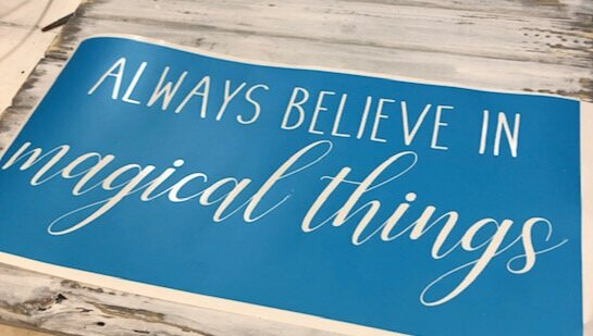 blue translucent stencil saying always believe in magical things. The top line of the stencil reads always believe in, is shown in a skinny rae dunn inspired font. The second bottom line magical things is shown in a cursive style font with the letters connecting. The stencil is sitting on a white plank style table top.