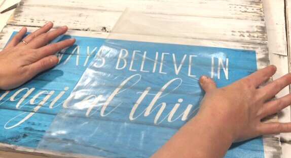 applying a stencil to a pallet style sign with clear transfer tape. blue translucent stencil saying always believe in magical things. The top line of the stencil reads always believe in, is shown in a skinny rae dunn inspired font. The second bottom line magical things is shown in a cursive style font with the letters connecting. The stencil is sitting on a white plank style table top.