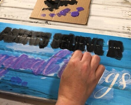 stenciling on a wood pallet style sign. Blue translucent stencil film is used for the stencil that reads always believe in magical things. Women is using black and purple acrylic craft paints to paint the lettering of the stencils. She is using a piece of cardboard to hold her paint and dabbing a cosmetic sponge into the paint to paint on the stencil.