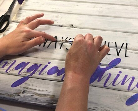 women is using an xacto knife to help remove translucent blue oramask stencil film from a wood pallet style sign. The stencil lettering is painted in black and purple and reads always believe in magical thins. There are a pair of scissors in the background. Pallet sign is painted in rustic distressed white.