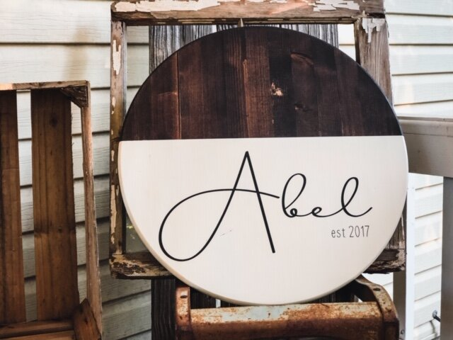 dark stained round wood disc sign. Sign is half stained in dark Kona and half painted in cream. Sign reads Abel est 2017 and is sitting on a rusty metal chair with an old window behind the wood sign