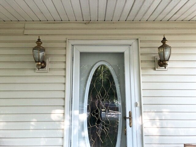 outdated brass colored front porch lights. Siding is light yellow in color. Front and screen doors are white.