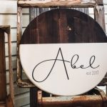 Rustic farmhouse round last name sign with established date. Black lettering. Half stained half painted in chalk paint white. Sitting on a rusty metal chair with an old window behind it and a wood crate off to the side on a front porch.