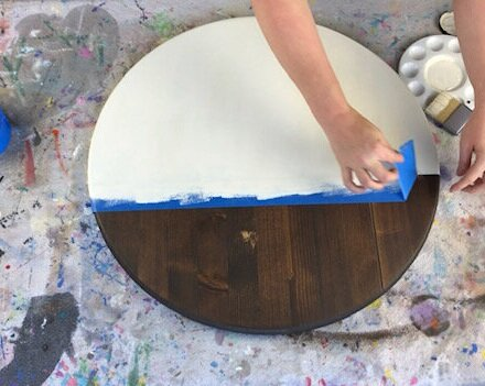 Women peeling up tape on a painted wood sign. Dark stained round disc wood sign partially painted in an off white cream color. Taped off with wide blue painter's tape. Paint pallet and wide paint brush are on the drop cloth table covering. Waiting for the paint to dry on the last name wood sign.