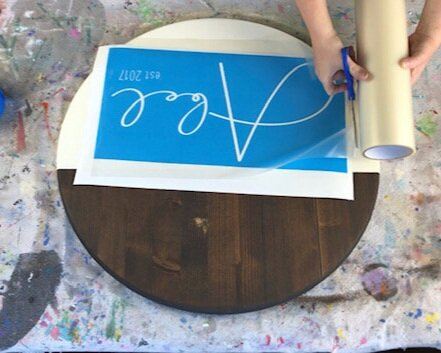 Women using scissors to cut clear transfer tape to apply  applying transfer tape to a blue personalized last name stencil for a round painted wood sign. Round wood disc is dark stained, Kona, and partially painted in an off white cream color.