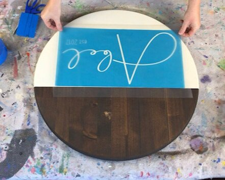 Women applying a personalized blue stencil that has clear transfer tape on it to a round stained and painted wood disc base. Blue vinyl squeegee and a paint splattered drop cloth to keep the table surface clean in the background.