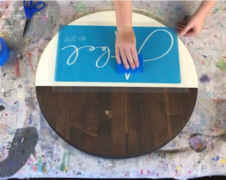 Women using a blue vinyl squeegee to press out air bubbles on a personalized blue stencil.