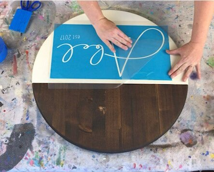 Women making a round disc personalized painted wood sign. Peeling clear transfer off of a blue stencil. Dark stained wooden circle with off white cream color paint on the bottom half of the wood sign. Vinyl squeegee and painted drop cloth in the background.