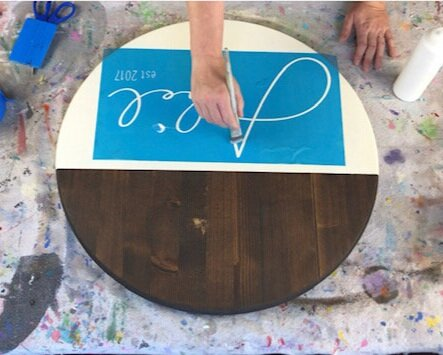 Women using a small paintbrush to apply clear matte finish mod podge to a stencil. Preventing paint bleed under the stencil. Round dark stained wood disc sign with an off white cream color bottom portion of the sign.  Blue vinyl squeegee and a paint splattered drop cloth on the table.