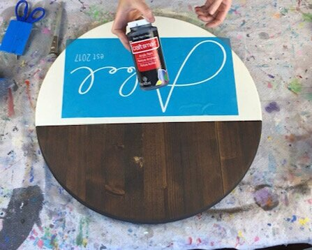 Using classic black acrylic paint to paint a personalized wood disc round sign. Wood stained in dark Kona. Stencil is blue translucent