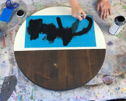 Women painting a personalized sign with black acrylic paint. Stencil is a translucent blue. Blue vinyl squeegee, scissors, drop cloth are also pictured.
