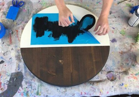 Woman making a painted wood sign. She is peeling the blue translucent stencil up that covers the bottom portion of the round wood disc sign. Wood is stained in a dark Kona color. Painted portion of the sign is off white cream colored. Lettering is painted in black. Roll of tape, paint bottle, scissors, vinyl squeegee, and a drop cloth.