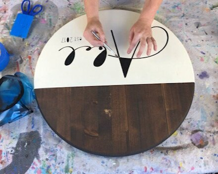 Women using an xacto knife to remove the middle pieces of the stencils off of the painted wood sign. Sign is stained in a dark Kona with off white cream colored paint. Lettering is painted in black.