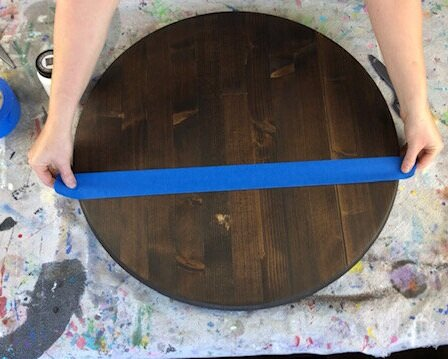 making a round painted wood sign. Wood is stained in a dark brown, Kona. Using blue wide painter's tape to tape off an area on the circle board to paint. Background is a paint splattered drop cloth to protect the surface of the table.