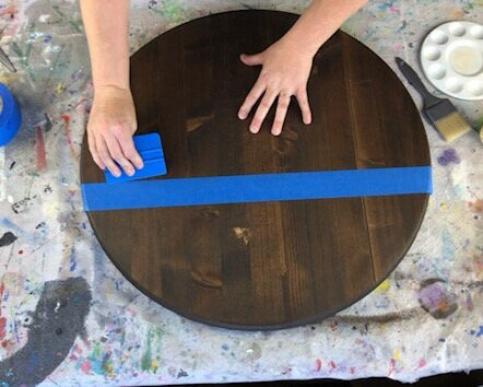 Dark stained wood, Kona in color, being prepped for painting. Woman has taped off the sign using wide blue painter's tape. She is using a blue vinyl squeegee to press out any air bubbles that are under the tape. Paintbrush and paint pallet on the paint splattered drop cloth that is covering the table.