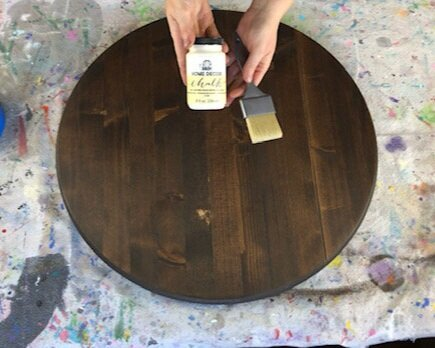 Round stained wood base, in the color Kona, used for making painted wood signs. Women is holding a bottle of chalkpaint, in the color sheepskin. A light beige off white color. She is also holding a wide paintbrush for painting signs or general crafts. Wood circle disc is setting on a paint spattered drop cloth to keep the table protected from craft projects.
