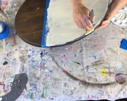 Women painting a wood sign. Round dark stained, in the color Kona, wooden disc taped off with blue wide painter's tape. She is using a downward motion to paint the wooden sign with chalk paint. The sign is sitting on a drop cloth to protect the table from craft projects.