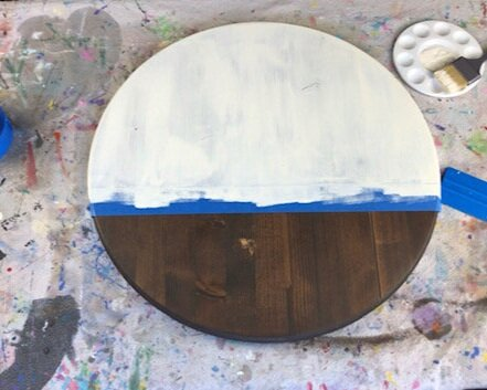 Dark stained round disc wood sign partially painted in an off white cream color. Taped off with wide blue painter's tape. Paint pallet and wide paint brush are on the drop cloth table covering. Waiting for the paint to dry on the last name wood sign.
