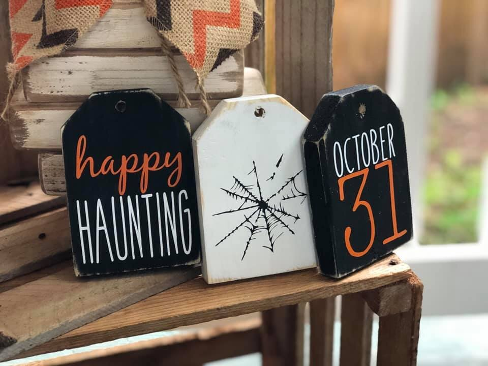 set of three Halloween themed wood tags. Black tag with cursive and skinny fonts reading happy haunting, white wood tag with the image of a spider web, black wood tag with orange and white skinny font lettering reading OCTOBER 31