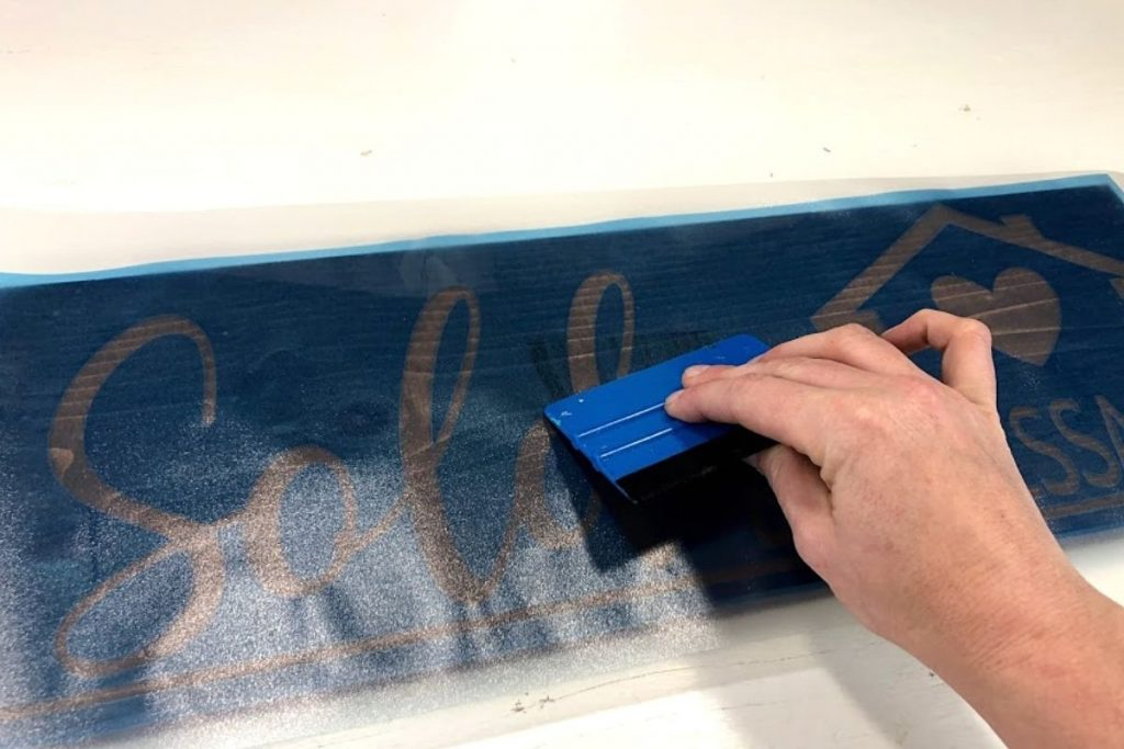 woman is using a blue vinyl squeegee to press out any bubbles that are on the stenciled wood sign. Stencil is a translucent blue and made from Oramask stencil film. Stencil reads Sold by Melissa with an image of a house and a heart.